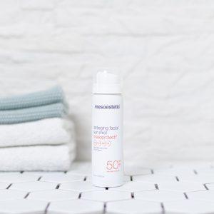 spray med solbeskyttelse creme på et badeværelse med håndklæder i baggrunden