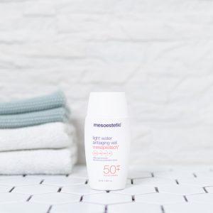tuben med solbeskyttelse spf 50 creme på et badeværelse med håndklæder i baggrunden