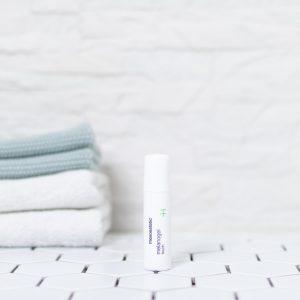 lille stift med pigment reducerende creme på et badeværelse med håndklæder i baggrunden