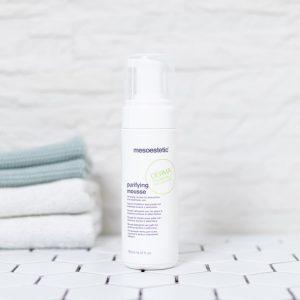 tuben med purifying creme på et badeværelse med håndklæder i baggrunden